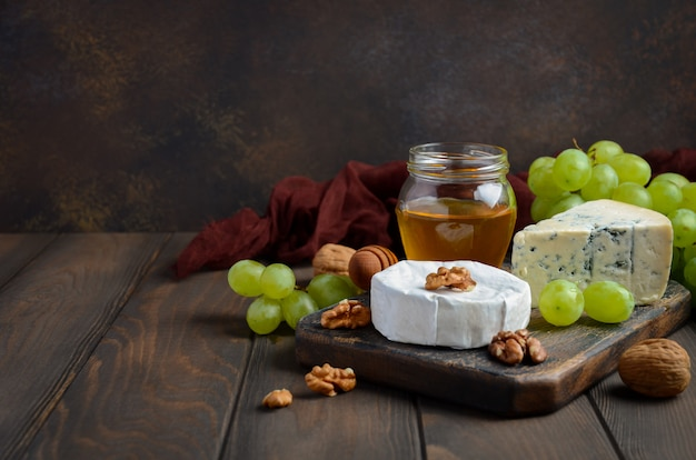 Assiette de fromages aux raisins, miel et noix sur fond sombre. Photo Premium