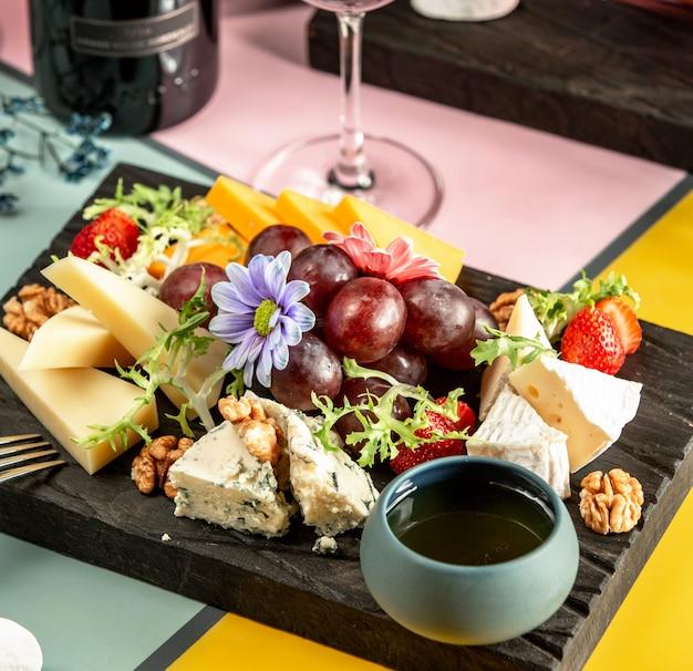 Assiette de fromages avec cheddar, chèvre, gouda, fromage bleu, miel, raisin et fleurs Photo gratuit
