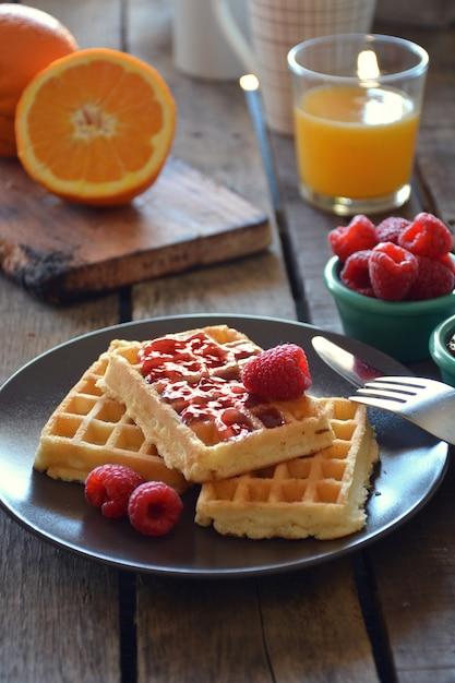 Assiette de gaufres à la marmelade de framboises, jus d'orange et café Photo Premium