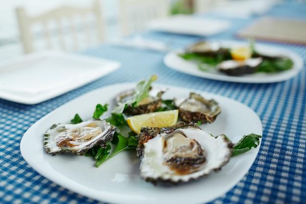 Assiette D'huîtres Crues Fraîches, De Salade Verte Et De Citron Dans Un Café En Plein Air Photo Premium
