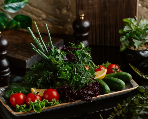 Une assiette de légumes de saison frais comprenant des tomates, des concombres et une variété de verdure Photo gratuit