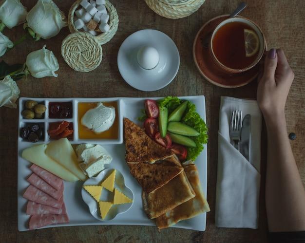Assiette de menu du petit déjeuner avec un grand choix d'aliments et une tasse de thé Photo gratuit