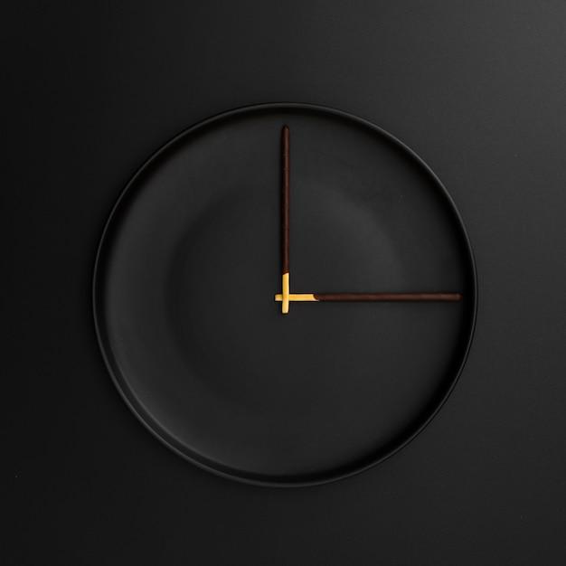 Assiette noire avec bâtons de chocolat en forme d'horloge Photo gratuit