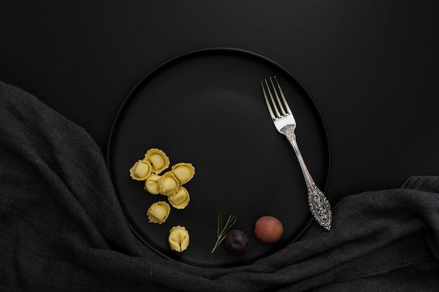Assiette noire avec tortellini et fourchette sur fond noir Photo gratuit