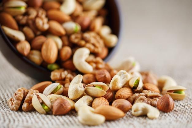 Une assiette de noix renversée sur le fond d'un vêtement de toile de jute Photo Premium