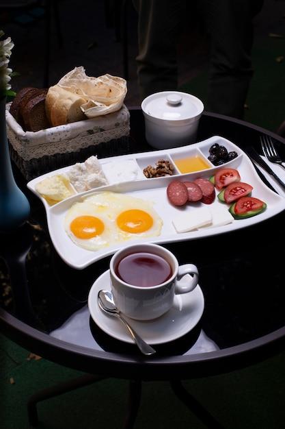 Assiette de petit-déjeuner avec une variété d'aliments, une tasse de thé et du pain. Photo gratuit