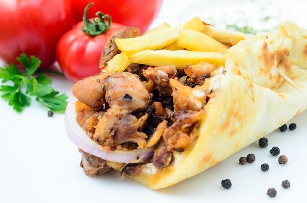 Assiette de pita gyros grecque traditionnelle avec de la viande, des pommes de terre frites, de la tomate et de l'oignon Photo Premium