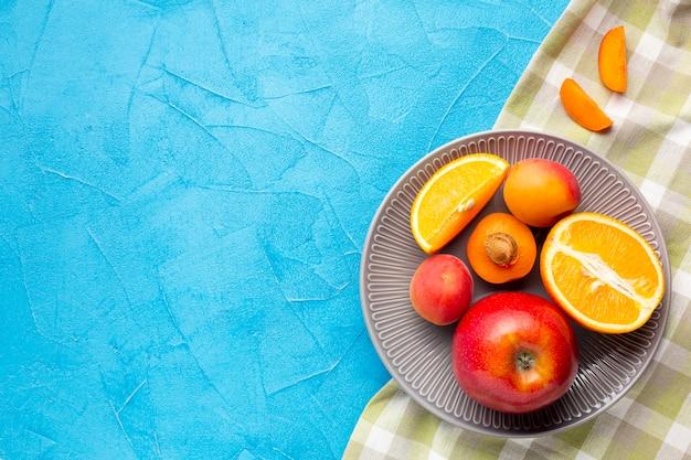 Assiette plate de baies fraîches et de fruits avec fond Photo gratuit