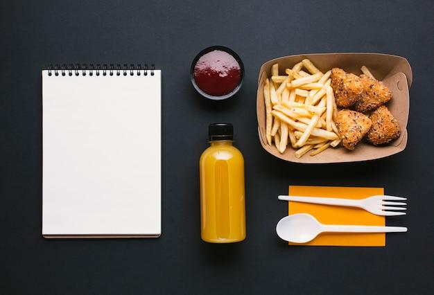 Assiette plate avec frites et cahier Photo gratuit