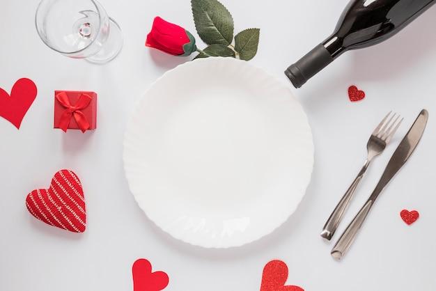 Assiette près de coeurs bouteille, verre, fleur et ornement Photo gratuit