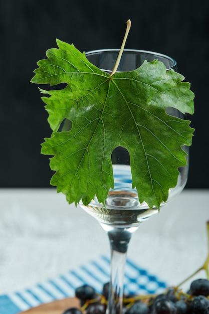 Une Assiette De Raisins Noirs Et Un Verre De Vin Avec Des Feuilles Sur Un Tableau Blanc, Gros Plan Photo gratuit