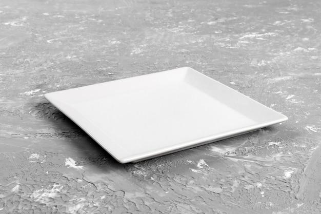 Assiette rectangulaire vide sur fond de table gris Photo Premium
