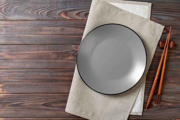 Assiette ronde grise vide avec des baguettes pour sushi sur bois Photo Premium