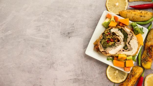 Assiette avec rouleau de poulet et légumes sur une table en béton Photo gratuit
