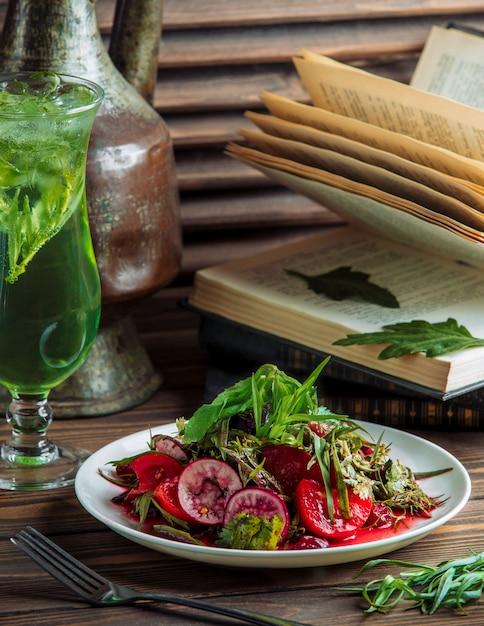 Une assiette de salade de légumes avec un verre de jus vert. Photo gratuit