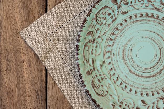 Assiette de secours vintage vide sur une serviette en lin sur table en bois de planche, vue de dessus, modèle de menu Photo Premium