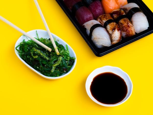 Assiette De Sushi Noir Avec Salade D'algues Et Sauce Soja Sur Fond Jaune Photo gratuit