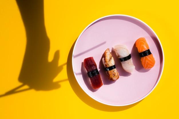 Assiette de sushi avec une ombre de baguettes Photo gratuit