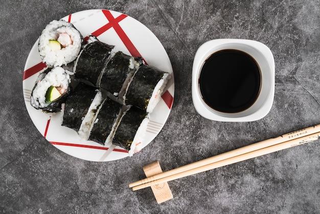 Assiette avec des sushis près de la sauce soja et des baguettes Photo gratuit