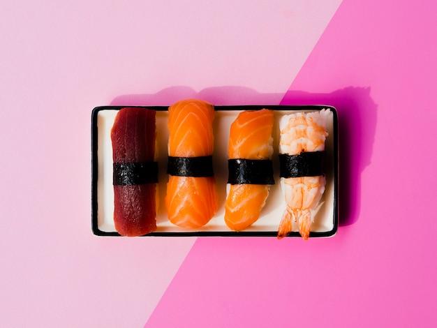 Assiette de sushis variaton sur fond rose Photo gratuit