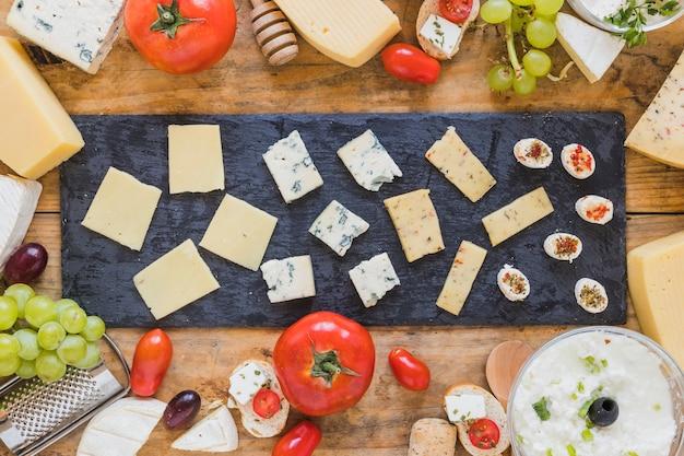 Assiette de tranche de fromage sur ardoise noire au-dessus de la table Photo gratuit