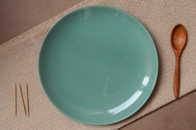 Assiette verte et cuillère en bois sur une nappe crème prête à manger Photo Premium