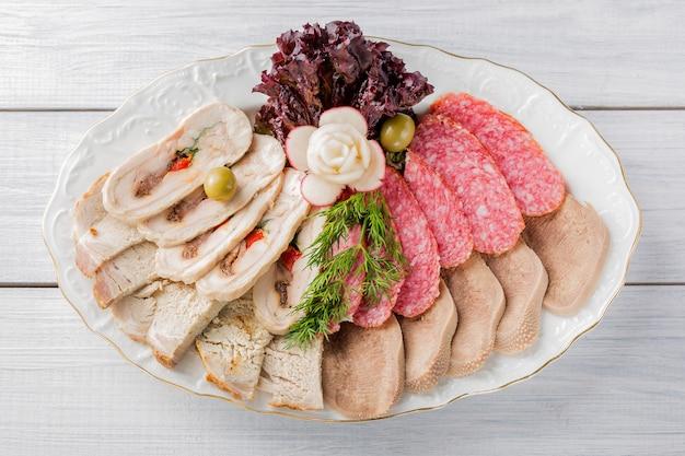 Assiette de viande avec de délicieux morceaux de jambon en tranches, saucisse, olives, langue de boeuf, herbes et viande avec radis sur une assiette blanche et une table en bois Photo Premium