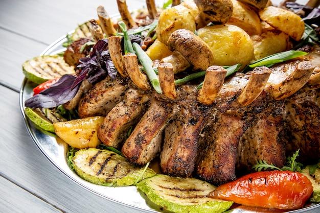 Assiette de viande avec de délicieux morceaux de viande, salade, côtes levées, légumes grillés et pommes de terre sur une table en bois blanche Photo Premium