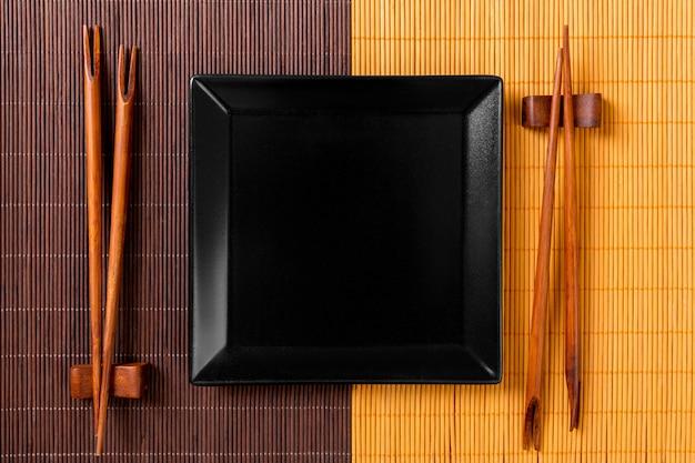 Assiette vide en ardoise carrée noire avec des baguettes pour sushi sur bois Photo Premium