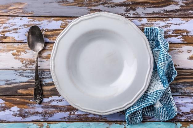 Assiette vide blanche sur une vieille table en bois, concept de fond bleu Photo Premium
