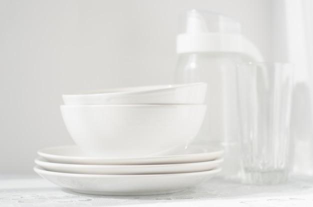 Assiettes blanches et bols sur la table lumineuse Photo Premium