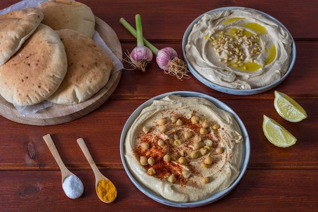 Assiettes de houmous avec du pain pita sur fond rouge en bois Photo Premium