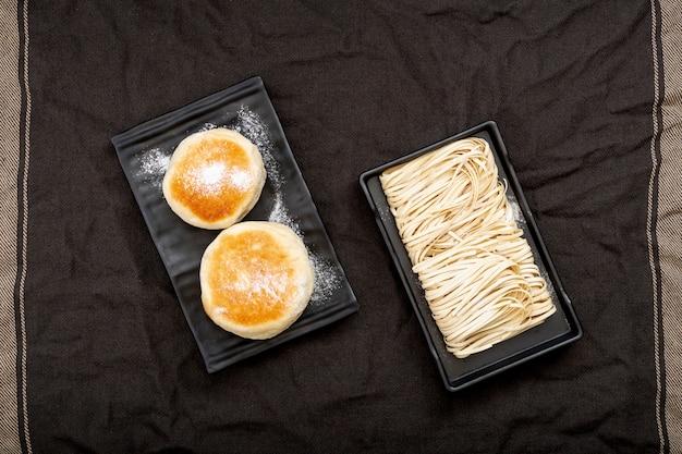 Assiettes noires avec des nouilles et des muffins sur un drap noir Photo gratuit