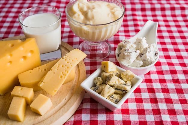 Assiettes et planche à découper avec du fromage frais près du verre de boisson Photo gratuit