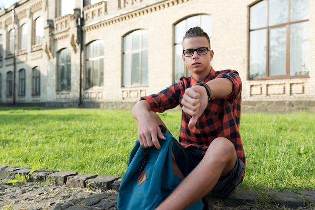 Assis adolescent garçon regardant la caméra désapprouver Photo gratuit