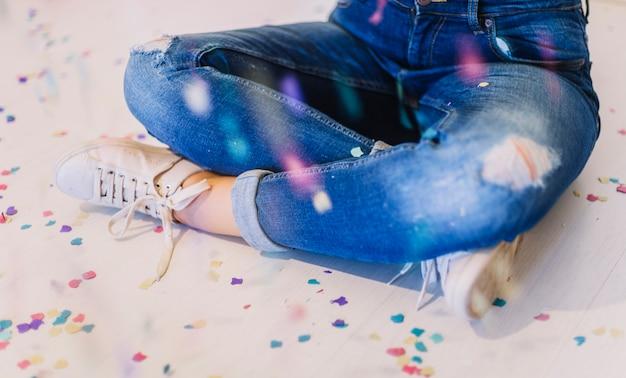 Assis sur le sol entouré de confettis Photo gratuit