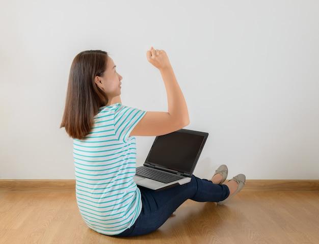 Assis sur le sol avec un ordinateur portable levant les bras avec un regard de succès Photo Premium