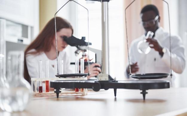 Assistant De Laboratoire Avec Ampoule De Verrerie De Laboratoire Microscope Avec Des Produits Chimiques. Photo gratuit