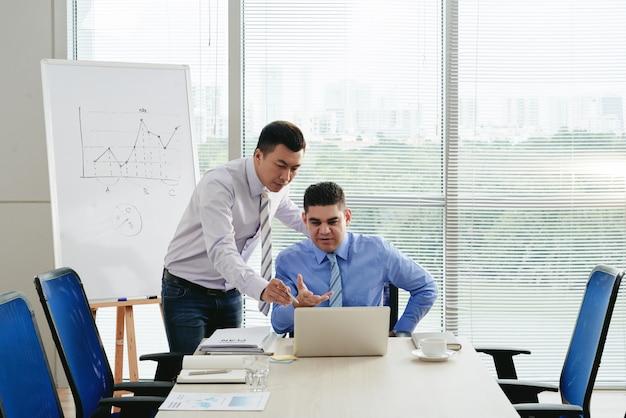 Associés d'affaires examinant le rapport financier numérique Photo gratuit