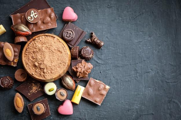 Assortiment de chocolat et de poudre de cacao sur fond noir Photo Premium