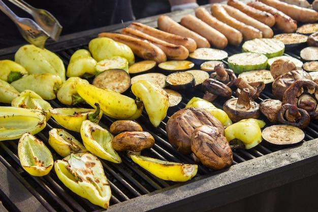 Assortiment de délicieuses viandes grillées avec des légumes sur le barbecue sur le charbon de bois. saucisses, steaks, poivrons, champignons, courgettes. Photo Premium