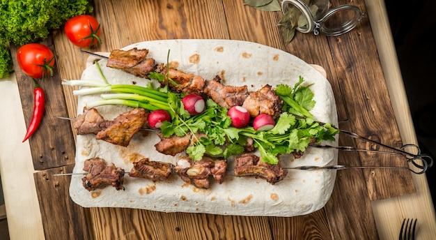Assortiment de délicieuses viandes grillées avec des légumes sur une table de pique-nique avec une assiette blanche Photo Premium