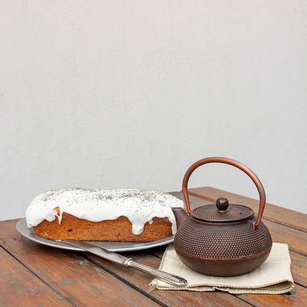 Assortiment avec un délicieux gâteau et une vieille théière Photo gratuit