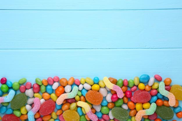 Assortiment de divers bonbons et gelées sur fond bleu Photo Premium