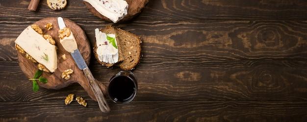 Assortiment de fromages sur assiette en bois, pain et vin Photo Premium