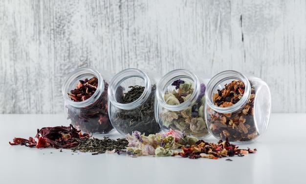 Assortiment D'herbes Séchées Dans Des Bocaux En Plastique Sur Une Surface Blanche Et Grunge Photo gratuit