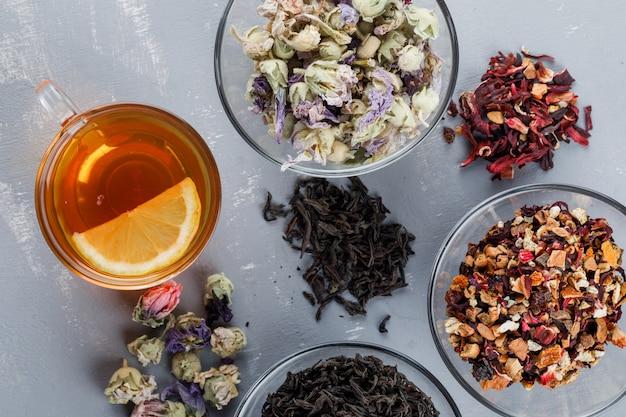 Assortiment D'herbes Séchées Dans Des Bols En Verre Avec Une Tasse De Thé à Plat Sur Une Surface En Plâtre Photo gratuit