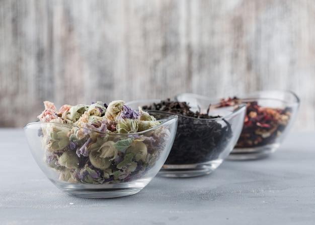 Assortiment D'herbes Séchées Dans Des Bols En Verre Vue Grand Angle Sur Le Plâtre Et La Surface Grungy Photo gratuit