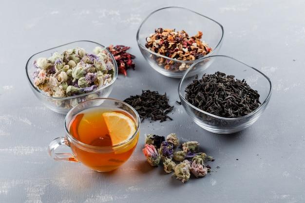 Assortiment D'herbes Séchées Avec Tasse De Thé Dans Des Bols En Verre Sur La Surface En Plâtre Photo gratuit