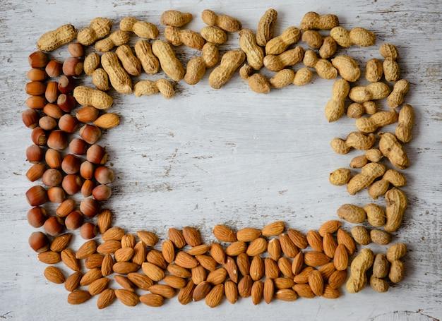 Assortiment de noix sur un fond en bois. fond de mélange de nourriture, vue de dessus, espace copie, bannière Photo Premium